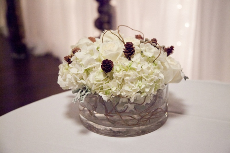 a rustic and cozy winter wedding centerpiece of white blooms, twigs and pinecones in a large vase