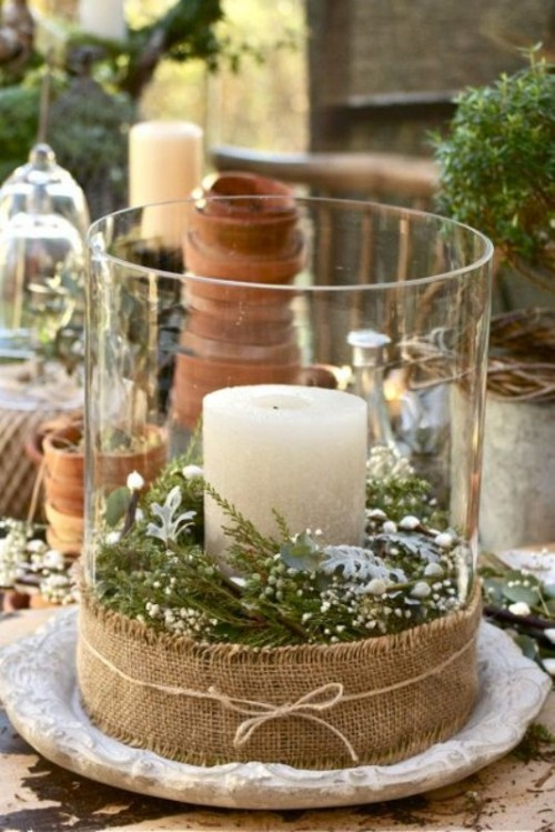 a simple and rustic winter wedding centerpiece in a large candleholder with burlap, evergreens and a pillar candle