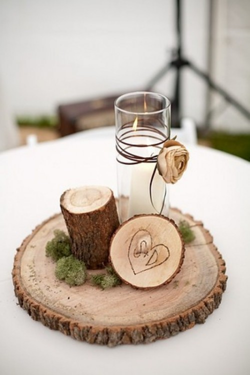 a rustic winter wedding centerpiece of a wood slice, a wood stump, a burnt wood slice and a candle with a fabric bloom