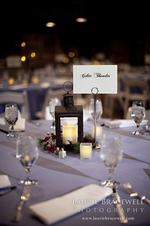 a mini winter wedding centerpiece of a candle lantern with greenery and berries is a cool and budget-friendly idea