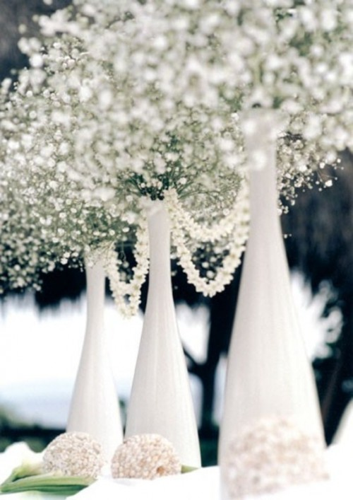 a white winter wedding centerpiece of bottles, baby's breath and pearl strands for a chic look