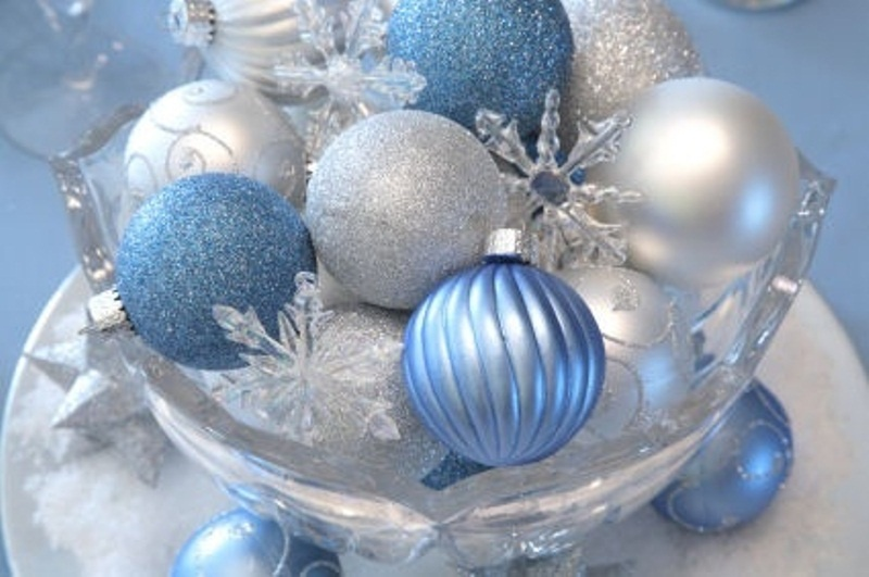 a blue and silver winter wedding centerpiece of ornaments in a glass bowl and snowflakes is easy to compose