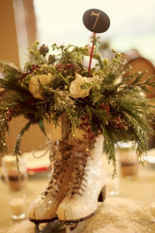 a creative winter wedding centerpiece of glitter skates with a lush evergreen, white bloom floral arrangement plus a chalkboard table number