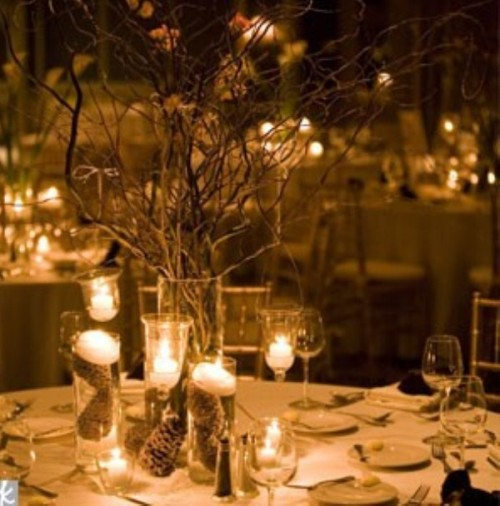 a stylish winter wedding centerpiece of glasses with pinecones inside and soem floating candles on top