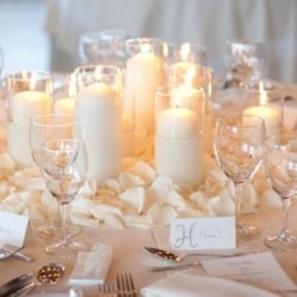 an elegant winter wedding centerpiece of white pillar candles and white petals will also fit other seasons as well