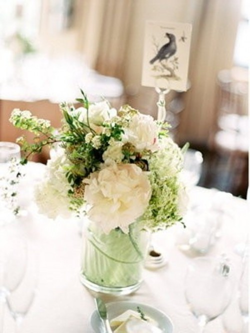 a stylish winter wedding centerpiece of white blooms, greenery and a leaf inside the vase