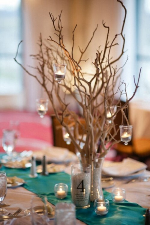 a unique winter wedding centerpiece of branches, glitter in the vase, some hanging candles