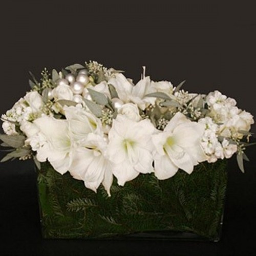 a formal winter wedding centerpiece of a bowl with evergreens, white blooms and large beads