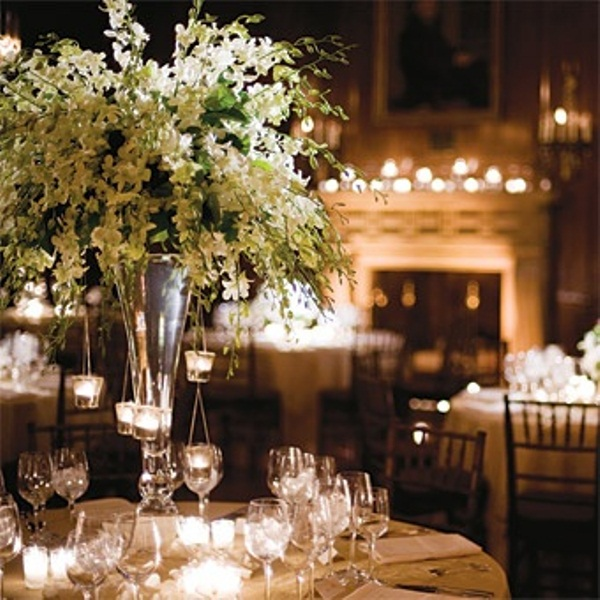 an oversized and lush white floral centerpiece in a tall vase with candles hanging on the branches