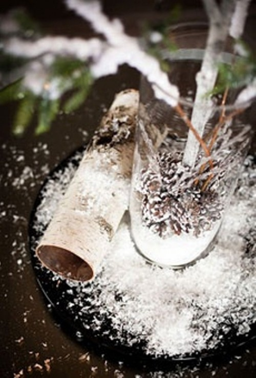 a rustic winter wedding centerpiece of branches and evergreens, snowy pinecones in the vase and bark