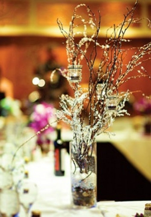 a frozen winter wedding centerpiece of branches and some candles hanging on them is a stylish and simple idea