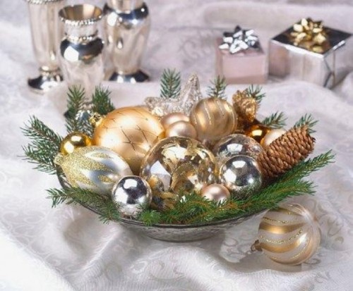 a holiday wedding centerpiece of a bowl with gold and silver ornaments and evergreens