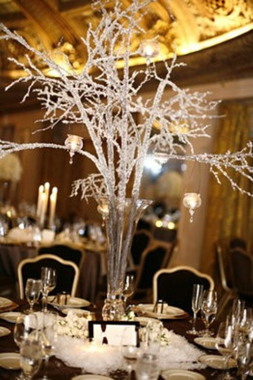 a winter wedding centerpiece of glitter branches in a tall vase and hanging candles on them