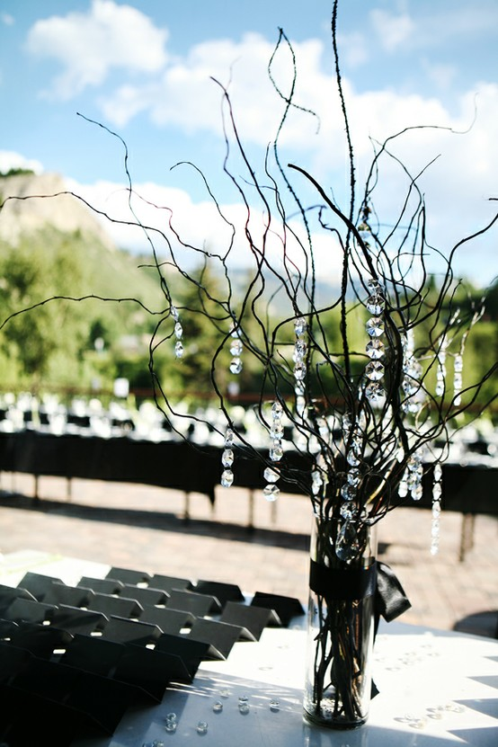 a stylish winter wedding centerpiece of black branches and crystals hanging gown from them