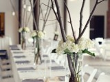 a simple and elegant winter wedding centerpiece of white hydrangeas and tall branches with candles hanging down