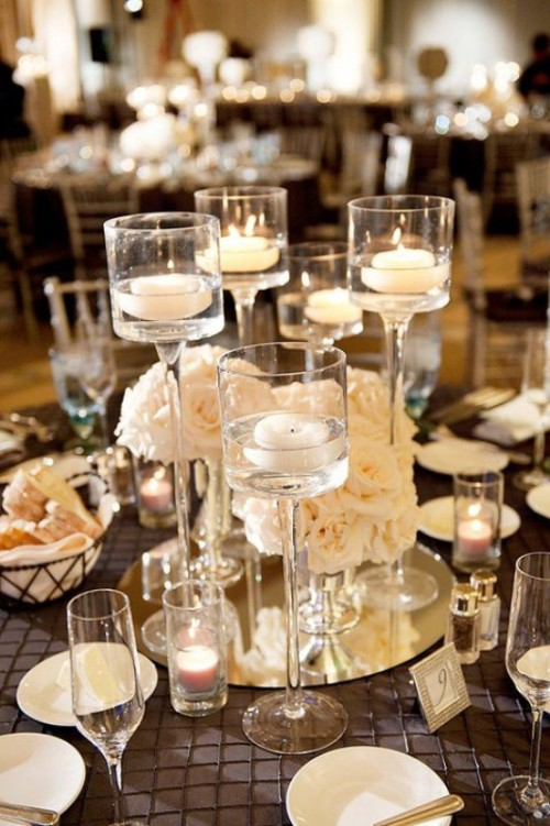 an elegant formal wedding centerpiece with white blooms and floating candles on a mirror