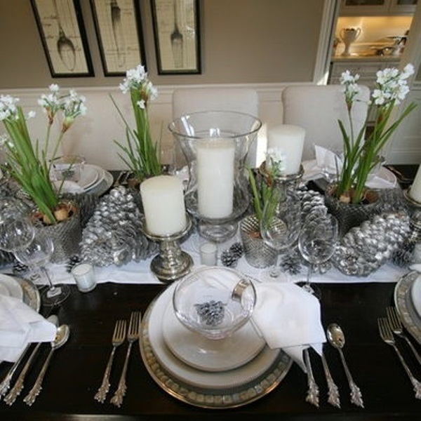 a winter wedding centerpiece of silver pinecones, white blooms, snowy pinecones and pillar candles