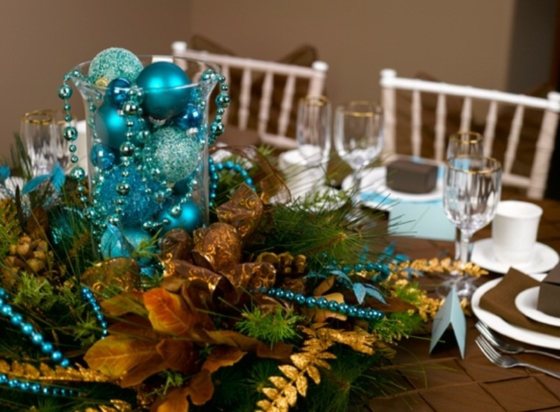 a colorful winter wedding centerpiece of a gilded pinecone, faux evergreens and gold ribbons and turquoise ornaments and beads