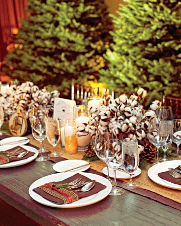 cozy winter wedding centerpiece of cotton arrangements and pillar candles plus wood slices feel cozy and rustic