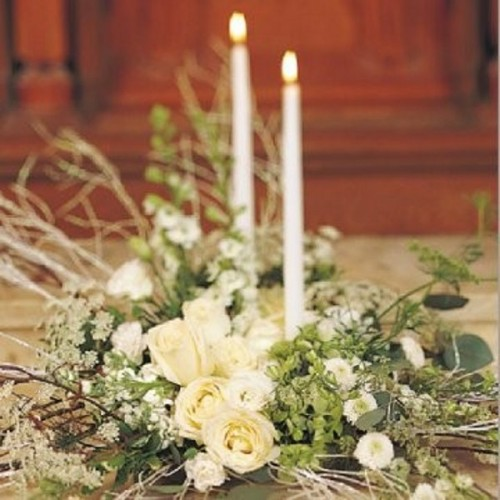 a white and green floral centerpiece with tall and thin candles is a stylish idea for a winter wedding
