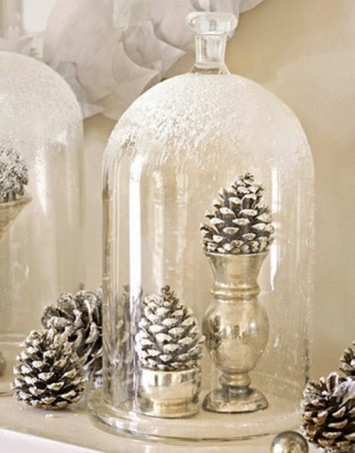 snowy pinecones in gold stands and in a snowy cloche on top is a stylish idea for a winter wedding