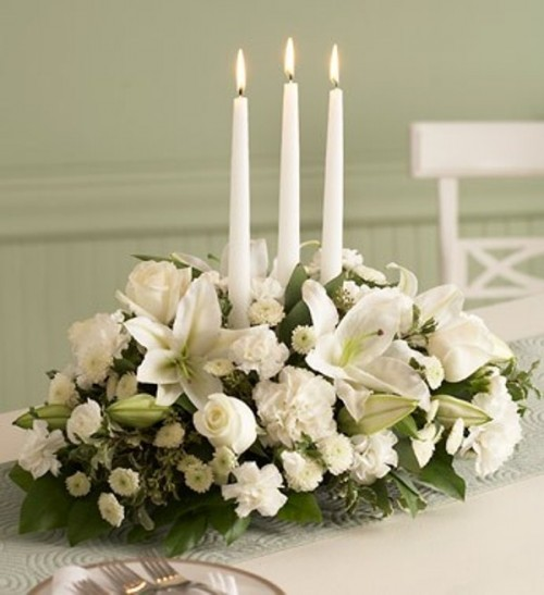 a refined winter wedding centerpiece of blooms and three thin and tall candles