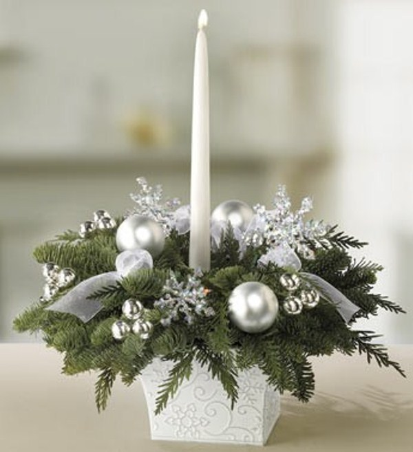 a winter wedding centerpiece of silver ornaments, snowflakes, evergreens and a tall and thin candles