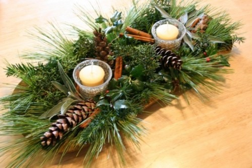 a wooden bowl with evergreens, pinecones, cinnamon sticks, candles and fresh greenery