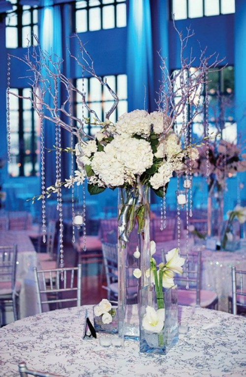 a winter wedding centerpiece of white blooms, with branches with crystals hanging down