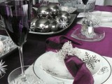 a bowl with dark Christmas ornaments and snowflakes is a winter wedding centerpiece