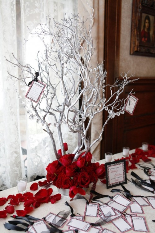 a winter centerpiece of silver branches with crystals and red roses looks dramatic and will fit a winter wonderland wedding