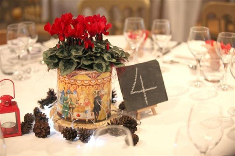 a bold winter wedding centerpiece of red blooms in a large box on a wood slice and pinecones around is a simple and cute idea