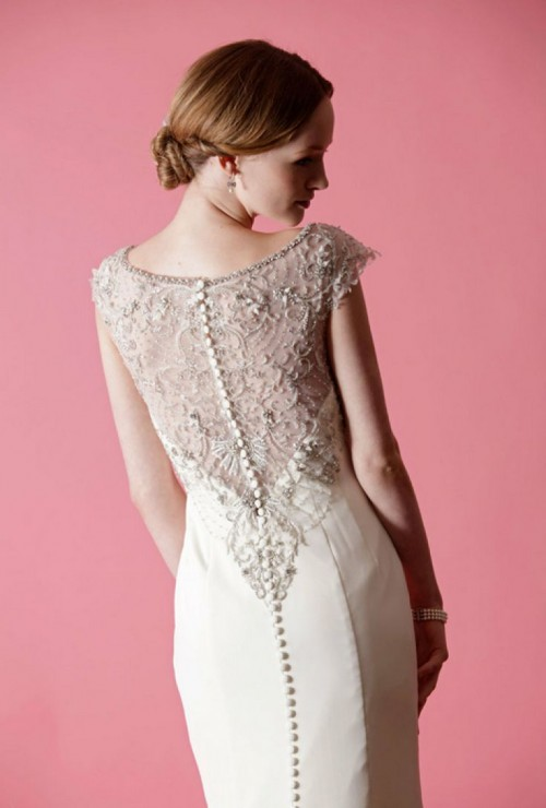 a refined fitting wedding dress wiht an illusion back of lace, rhinestones and a row of buttons, with cap sleeves and a high neckline