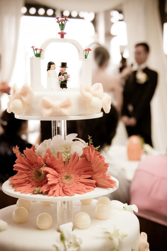 a white bow wedding cake with Lego figurines as cake toppers is a cool idea