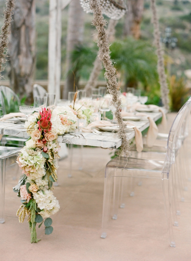 a lush neutral and bright floral garland with some greenery continues the beachy theme in decor