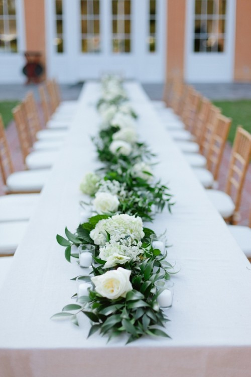 a greenery and white bloom table garland and some candles that match it