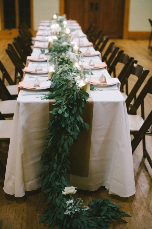a lush greenery table dotted with some white blooms here and there for a more elegant and chic look