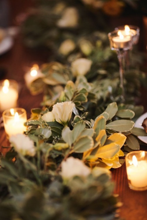 a beautiful greenery wedding table garland dotted with white blooms is a chic and bold idea