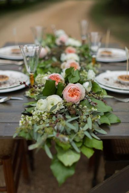 a lush greenery and peachy bloom table garland is a cool idea for a rustic or any other wedding