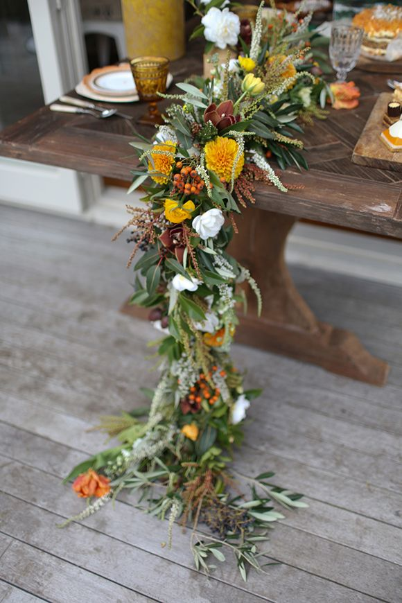 a textural fall inspired table garland with white, marigold and brown blooms looks refined and unusual