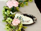a whimsy table garland of pink and green flowers is a creative idea for a spring or summer wedding