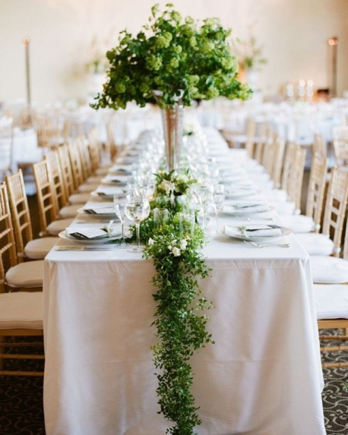 a greenery garland with some neutral blooms and a lush and tall greenery centerpiece enliven the table