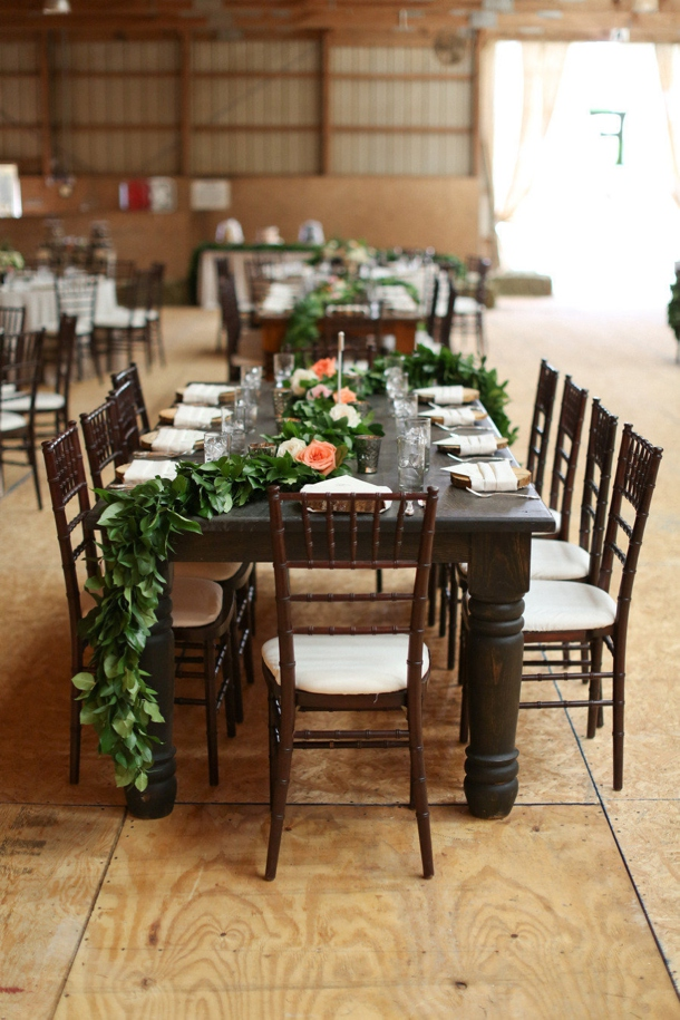a greenery garland with white and peachy blooms is a pretty rustic idea to decorate the table