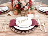 a floral centerpiece with burgundy and marsala blooms and marsala napkins make the tablescape chic and refined and bring elegance