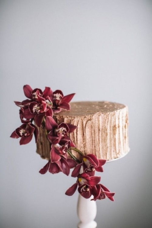 a gold wedding cake with plenty of texture and marsala blooms is a refined and beautiful dessert to rock