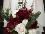 a beautiful dimnesional wedding bouquet of marsala, white blooms and creative and textural greenery and foliage