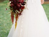 a refined and chic marsala and red wedding bouquet with greenery, foliage and other textural touches