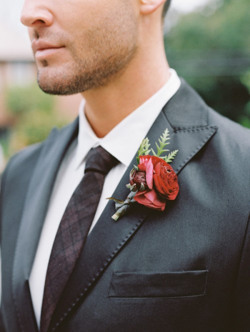 a red and marsala wedding boutonniere with greenery is a bright and chic accent for a fall groom's look