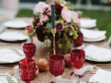 spruce up your wedding tablescape with marsala glasses, blooms and napkins to make it feel like fall and stand out with a colorful statement