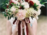 a beautiful wedding bouquet of white, blush and marsala blooms and some greenery plus marsala and blush ribbons, a lovely idea for the fall